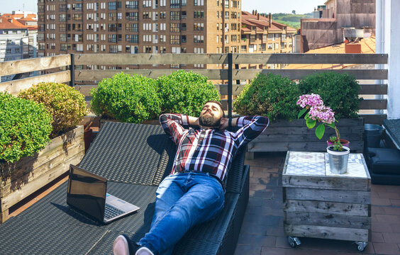 Businessman resting on lounger on terrace with laptop