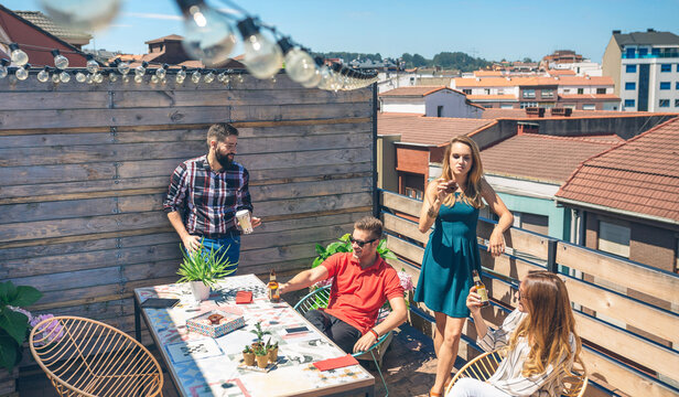Group of friends talking and drinking at a party on a terrace