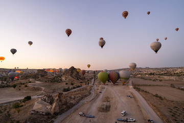 Cappadocia, Turkey : Wide angle shot of colorful hot air balloons together floating in the sky at early morning in Goreme