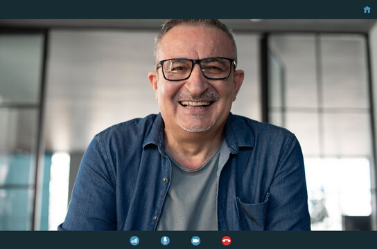 Senior man talking to webcam