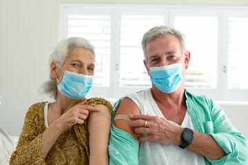 Fototapeta premium Smiling caucasian senior couple with plaster on arm after vaccination, wearing face masks