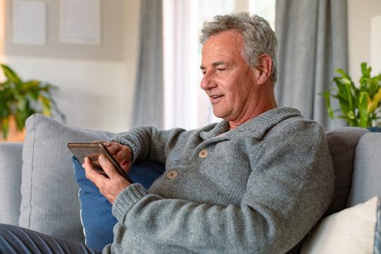 Happy caucasian senior man sitting on sofa and using tablet