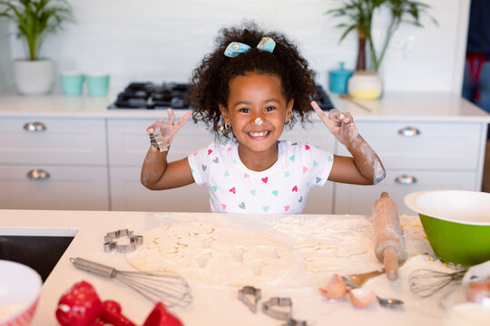 Happy african american messy girl baking in kitchen