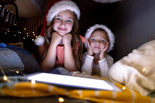 Happy caucasian siblings wearing santa hats and using tablet at christmas time