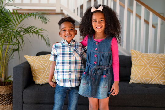 Happy african american sibling standing and looking at camera