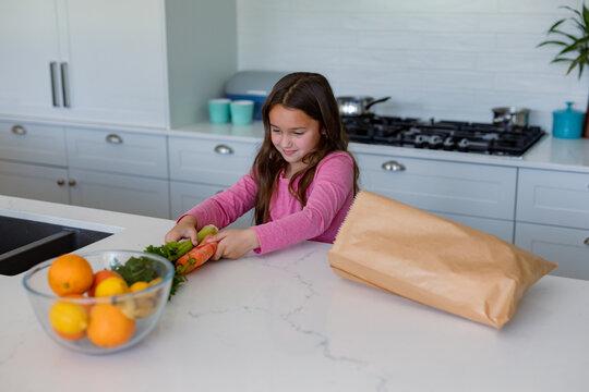 Happy caucasian girl unpacking groceries in kitchen