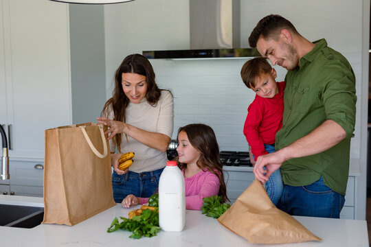 Happy caucasian family unpacking groceries together in kitchen