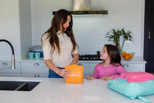 Happy caucasian mother and daughter preparing lunchbox to school in kitchen