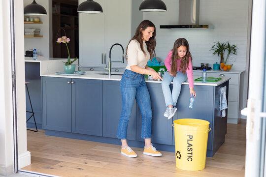 Happy caucasian mother and daughter segregating rubbish
