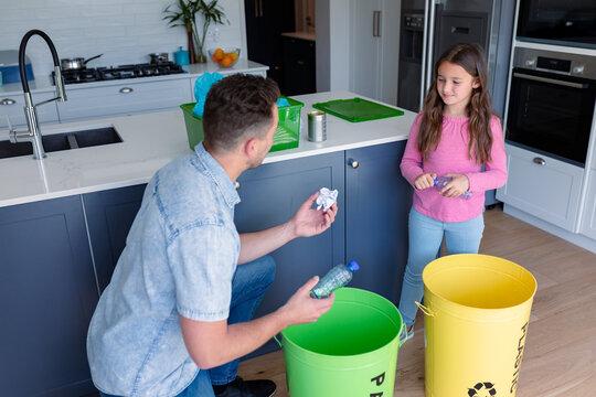 Happy caucasian father and daughter segregating rubbish