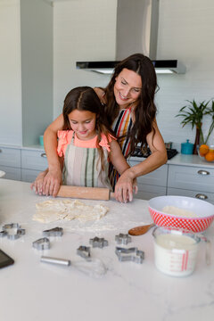Happy caucasian mother and daughter baking together, making cookies in kitchen
