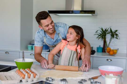 Happy caucasian father and daughter baking together, making cookies in kitchen