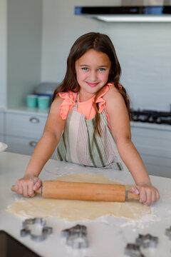 Portrait of happy caucasian girl baking, making cookie in kitchen
