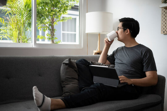 Casual Asian man sitting on comfortable sofa at home and drinking coffee at the morning.