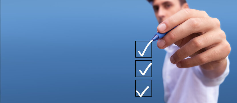 Young man checking boxes with list of 3 options on blue background