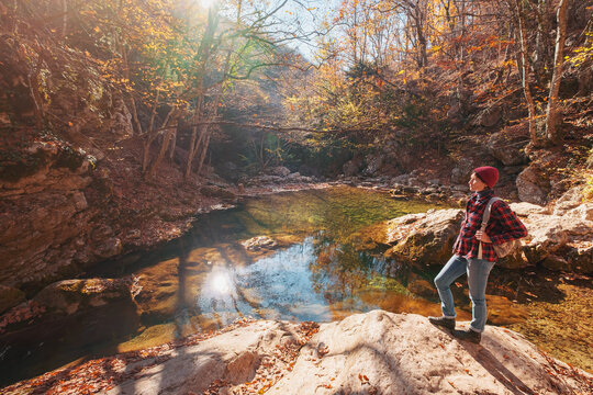 Woman hiking looking at scenic view of autumn foliage landscape.