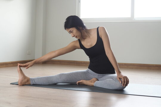 Slender Asian woman exercising and doing yoga at home