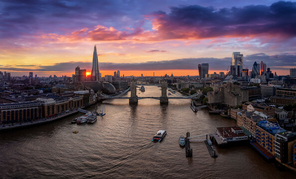Aerial view to the urban skyline of London with the Tower Bridge and skyscrapers of the City during a colorful sunset