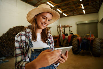 Fototapeta Caucasian female farmer smiling standing in shed holding digital tablet obraz