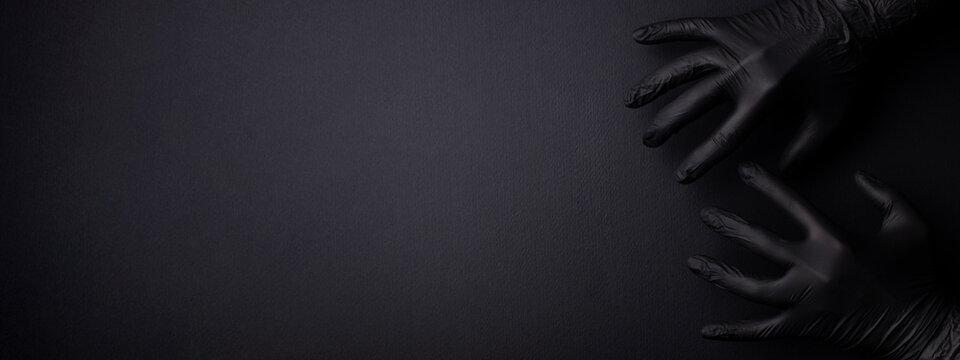 Black banner with hands in black gloves.
