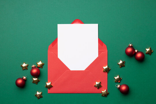 Mock-up with empty card in red envelope on green background with Christmas decorations.
