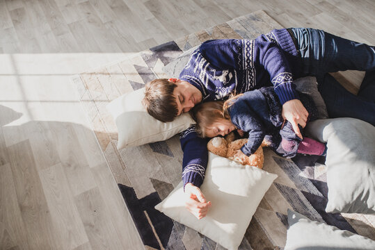 Father and little daughter at home play in christmas day dressed in traditional sweaters