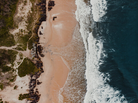 Drone shot of waves crashing on a beach from above