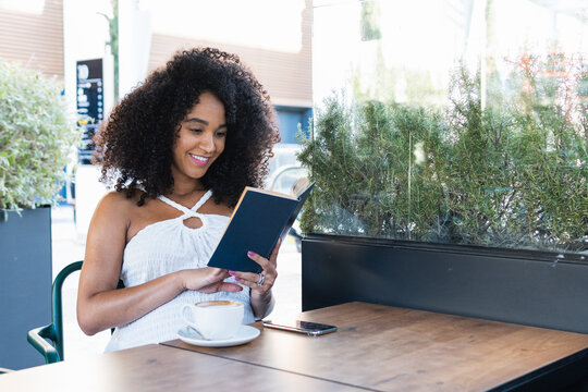 Pregnant black woman reading book and drinking coffee