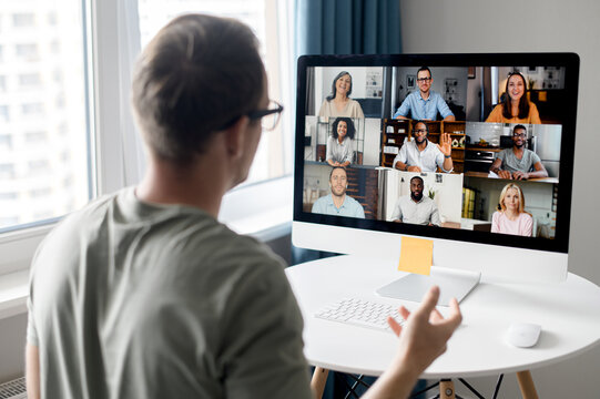 View from back above male shoulder on the laptop with diverse employees, coworkers on the screen, video call, online meeting. App for video conference with many people together