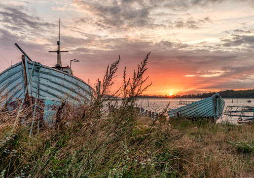 wooden boats moored on a beach meadow at sunset
