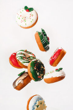 Flying Christmas donuts. Colorful doughnuts with sprinkles falling or flying in motion against white background.  Selective focus