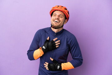 Fototapeta Young Brazilian cyclist man isolated on purple background smiling a lot obraz