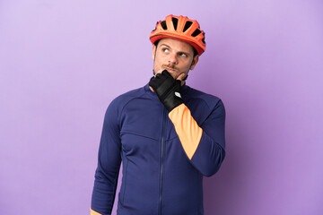 Fototapeta Young Brazilian cyclist man isolated on purple background and looking up obraz