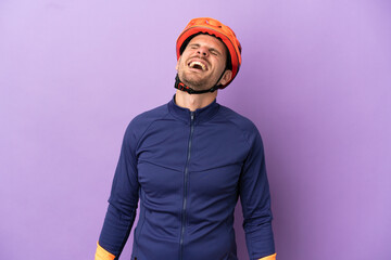 Fototapeta Young Brazilian cyclist man isolated on purple background laughing obraz