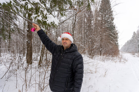 a man in a santa hat with a christmas ball in the winter in the forest