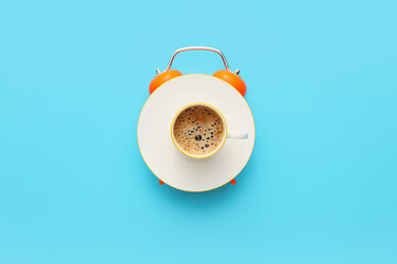 Fototapeta Creative alarm clock made with cup of coffee on blue background obraz