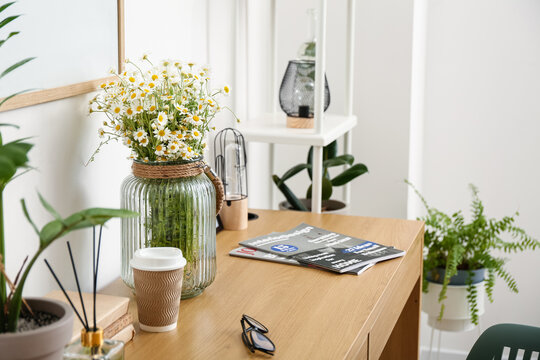 Modern workplace and vase with chamomiles near light wall
