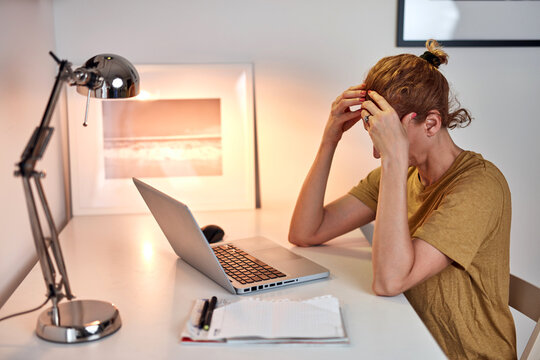 Woman working from home on a laptop and having headache.