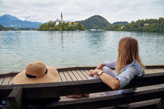 Young adult tourist woman sitting on a bench and enjoying on a lake.