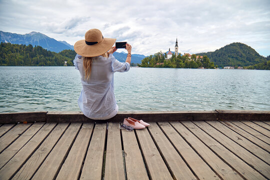 Young adult tourist woman enjoying on a lake while taking photos with a modern smartphone.