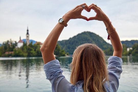 Female holding heart shape sign outdoors.