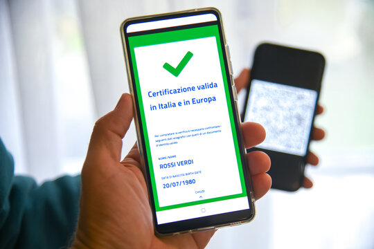 Checking the green pass on smartphone. Required for indoor tables in bar and restaurants, events and to access workplaces and company canteens. Valid certification.  Milan, Italy - September 2021