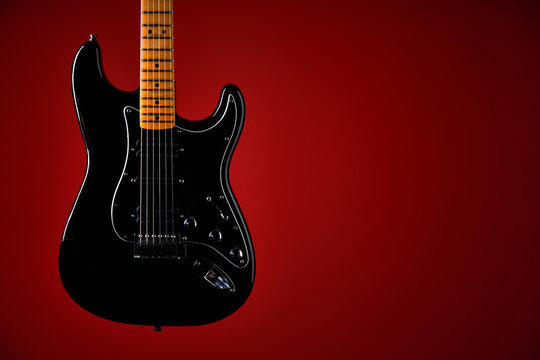 Black electric guitar on red background
