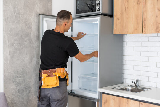 Young male worker repairing refrigerator
