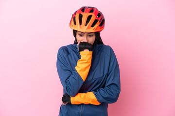 Fototapeta Teenager cyclist girl isolated on pink background having doubts obraz