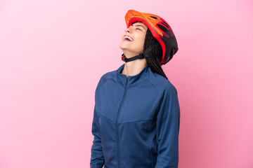 Fototapeta Teenager cyclist girl isolated on pink background laughing in lateral position obraz