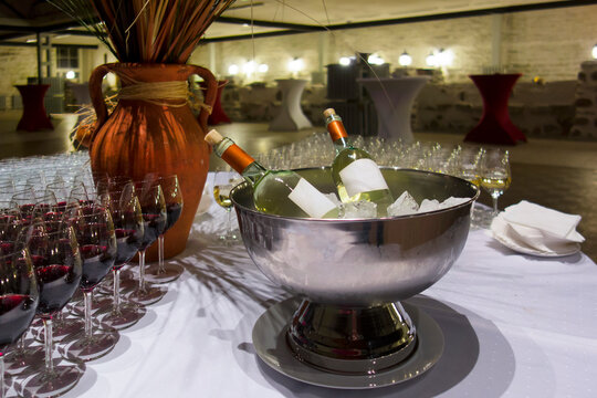 Wine bottles in metal ice bucket. Cooler with ice cubes. Wine glasses.