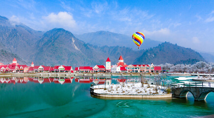 Colourful Hot Air Balloon rises above fairytale Xiling Snow Mountain landscape and resort - Chengdu, Sichuan, China