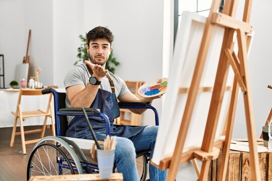 Young hispanic man sitting on wheelchair painting at art studio looking at the camera blowing a kiss with hand on air being lovely and sexy. love expression.