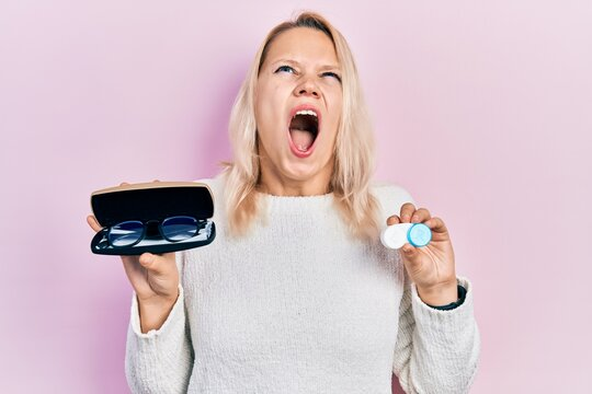 Beautiful caucasian blonde woman holding glasses and contact lenses angry and mad screaming frustrated and furious, shouting with anger looking up.